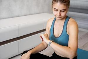 Portrait of young woman checking digital fitness tracker photo
