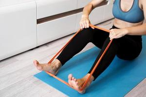 Young woman with elastic band. She trains her legs at home photo