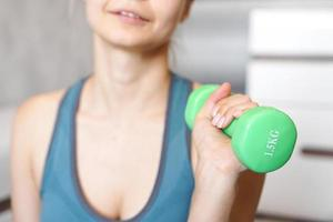 Sport and recreation concept - sporty woman hand with green dumbbell photo
