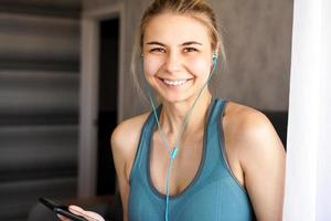 Young pretty sporty girl at home listens to music on headphones photo