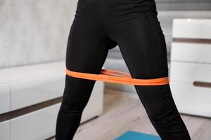 Woman during her fitness workout with rubber resistance band photo