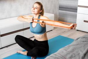 Woman trying to lose weight and have training with elastic band photo