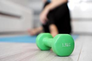 Close up of dumbbell and woman stretching in blurred background photo