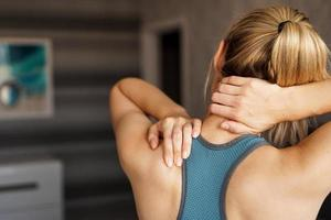 Sports injury concept. Athletic girl feeling pain in her neck photo