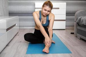 Unhappy woman sitting on the yoga mat with ankle injury, feeling pain photo