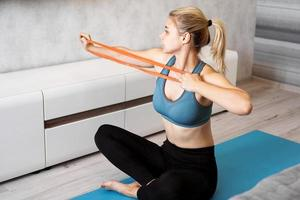 Woman at home trying to lose weight and training with elastic band photo