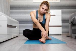 Infeliz mujer sentada en la estera de yoga con lesión en el tobillo, sintiendo dolor foto