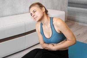 Portrait of young woman sitting on yoga mat, touching her stomach photo