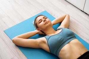 Top view of beautiful young woman lying on yoga mat after workout photo