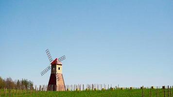 el típico molino de viento rojo parado en los campos. el paisaje rural foto