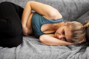 Side view of woman suffering from stomach ache lying on sofa at home photo