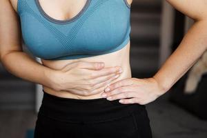 Close up of the woman holding her belly. Pain after home workout. photo