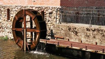 An old water mill on the background of a brick building. photo