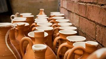 Close-up photo of clay jugs. Rows of handmade earthenware jugs