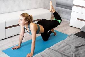 Pretty young trainer doing exercise, using dumbbells photo