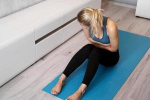 Fitness woman having pain in stomach during home workout photo
