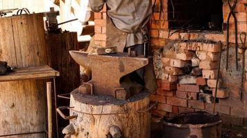 A blacksmith in an authentic workshop. Blacksmithing in the village photo