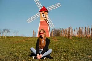 Beautiful young woman sits on the grass against the mill photo