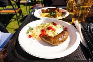 salchicha con ensalada en un plato y cerveza ligera en una bandeja. comida de la calle foto