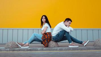 Confused young couple standing with one anothers back photo