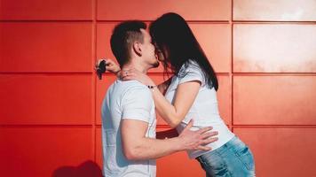 Pareja besándose contra la pared roja aislada en la ciudad foto