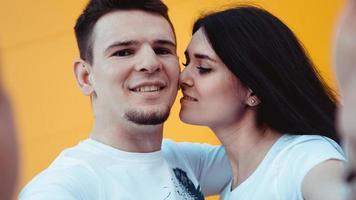 Encantadora pareja joven haciendo selfie en smartphone sobre fondo amarillo foto
