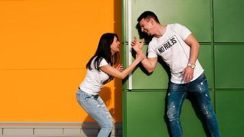 Young couple in love hiding from each other. The girl scared the guy photo