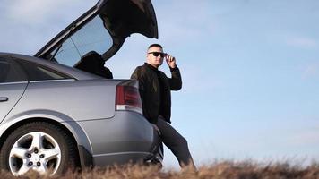 Vista sde del empresario en anteojos sentado en el maletero del coche foto