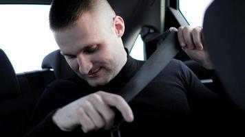 empresario en su coche abrocharse el cinturón de seguridad, concepto de conducción segura foto
