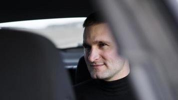 Smiling business man sitting in the back seat of a car photo