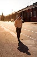Hipster caminando por la calle con edificio de pared de ladrillo rojo foto