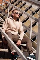 un joven se sienta en las escaleras de la ciudad. estilo urbano foto