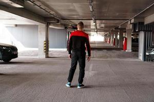 A young man in a sports uniform in an underground parking lot. photo