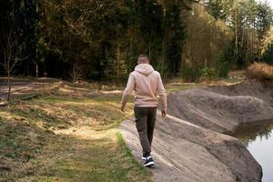 Un hombre camina por el bosque junto a un canal de remo o un río de montaña. foto