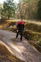 Young male athlete running in forest. Man jogging photo