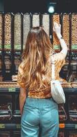 joven mujer positiva de pie junto a contenedores con nueces foto