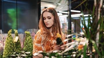Mujer joven comprando flores en un centro de jardinería foto