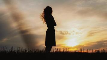 Silhouette of a young woman standing in dry grass field on sunset photo