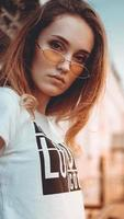 Fashion portrait stylish pretty woman in sunglasses posing in the city photo