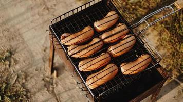 Deliciosas salchichas a la parrilla descansando sobre la rejilla de hierro foto