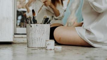 mujer pintora sentada en el suelo delante del espejo foto