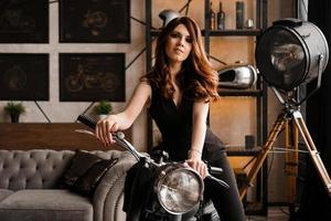Young woman with motorcycle in studio photo