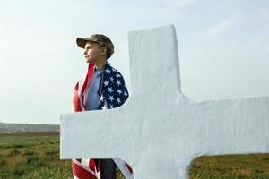 Joven con una gorra militar en la tumba de su padre en el día de los caídos foto