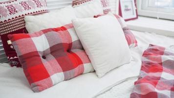 decoraciones navideñas de invierno. almohadas rojas blancas en la cama foto