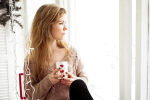 Beautiful young woman drinking coffee and looking through window photo