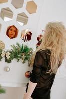 Una mujer bonita de cabello rubio en Navidad se encuentra cerca del espejo foto