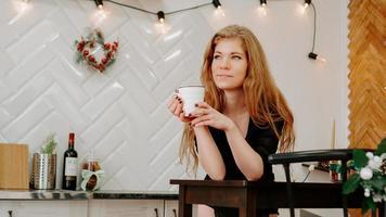 Mujer sostiene una taza de café por la mañana en la cocina de Navidad foto