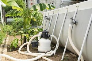Sand filter plant at a pool in the backyard photo