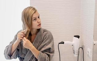 Woman brushing her hair and smiling while looking at the mirror photo