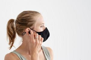 Young woman in a protective mask holding wireless earbuds photo